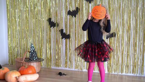 girl hold paper pumpkin mask. October Halloween holiday fest. 4K Live Action