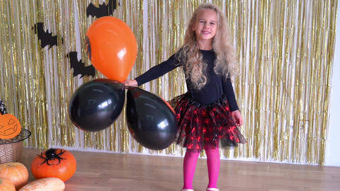 cute girl play with Halloween balloons on glitter pumpkin background GIF