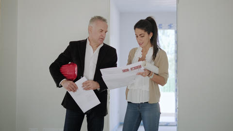 Man And Woman Checking House Project Plan In Construction Site Footage