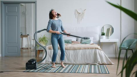 Joyful young girl singing and dancing using vacuum cleaner in bedroom Footage