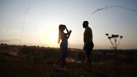 Silhouette of a charming young couple in love holding hands in the sunset light Footage