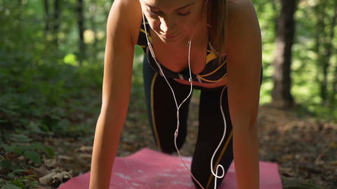 Attractive girl listening music on earphones while working out early in the Footage