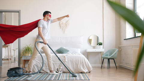 Guy in superman costume cleaning carpet with vacuum cleaner in bedroom at home Footage