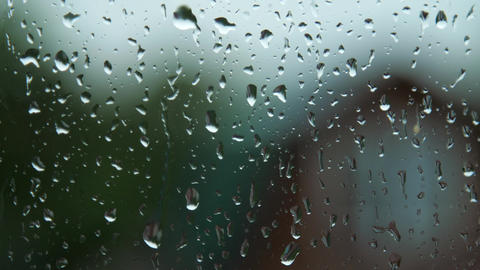 raindrop runs down on wet window surface under rain Footage