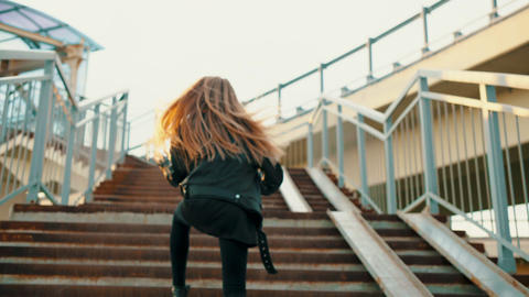 Teenage girl in leather jacket dancing on stairs Footage