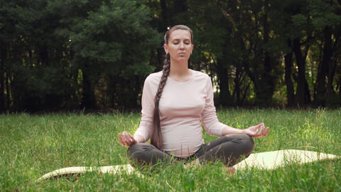 A pregnant woman practices yoga in the park sitting on a rug, sitting in the Live Action