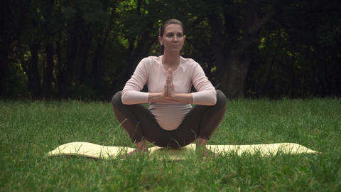 A pregnant woman practicing yoga in the park on a rug, doing the asana Malasana Live Action
