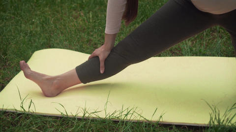Pregnant woman doing yoga in the park on the carpet, standing on one leg on the Live Action