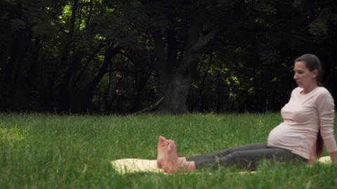 Pregnant woman doing yoga in the park on a rug, sitting with legs stretched Live Action