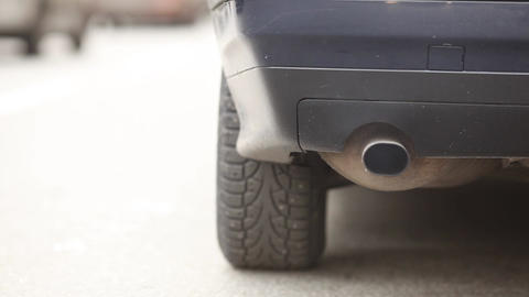 Close up view car exhaust pipe and wheel, vehicle move away with sound and smoke Footage