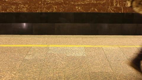 Unidentified passengers pass at empty subway platform. Loud ambient noise Footage
