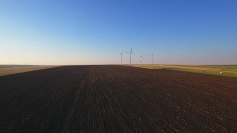 Aerial view of large wind turbines in a wind farm at sunset Filmmaterial