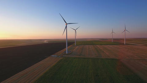 Aerial view of large wind turbines in a wind farm at sunset Footage