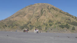 Tourists on horses with Gunung Batok volcano,Bromo,Java,Indonesia Footage
