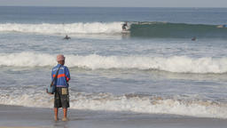 Fishing man and surfers in sea,Kuta,Bali,Indonesia Footage