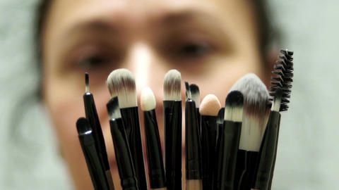 Woman Looking At Makeup Brushes Closeup ビデオ