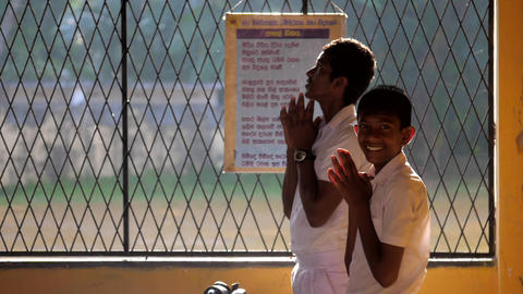 Sinhalese schoolboys in white uniforms pray slow motion Archivo