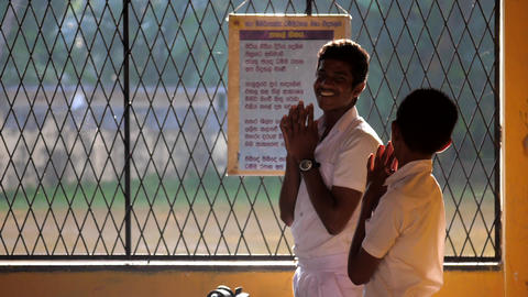 Sinhalese schoolboys lit by sun pray before lesson slow Archivo