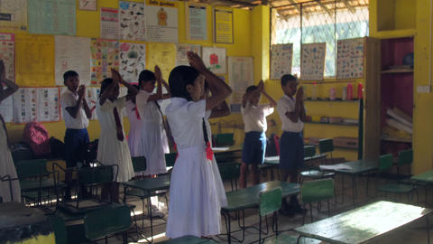 Sinhalese schoolchildren pray holding hands on heads Archivo