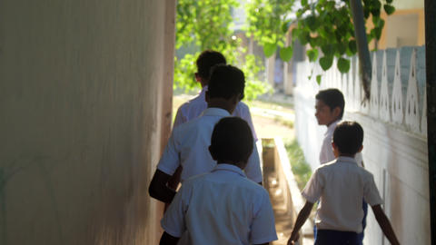 schoolboys in uniforms walk from building to schoolyard Archivo