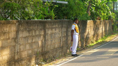 Sinhalese schoolboy stands at grey asphalt road slow Archivo