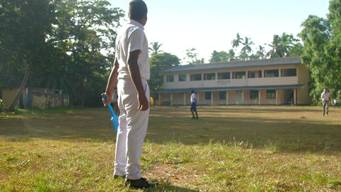 Sinhalese schoolboy in uniform holds cricket bat Archivo
