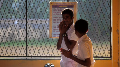 Sinhalese schoolboys pray against table with text Archivo
