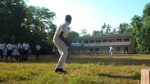 Sinhalese boy in white school uniform bats ball Archivo