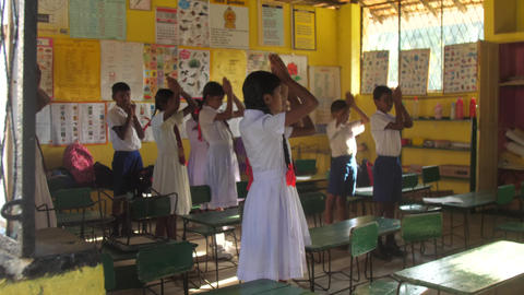 schoolchildren pray standing in classroom before lesson Archivo