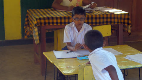 Sinhalese schoolboys in uniforms sit at wooden desk Archivo