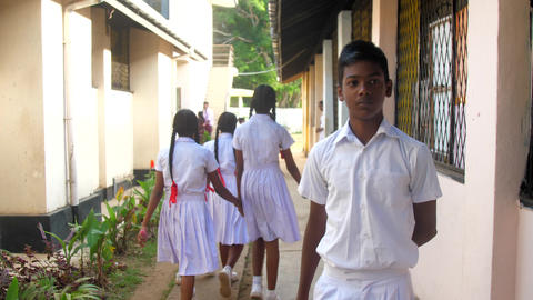 Sinhalese boys and girls walk between buildings Archivo