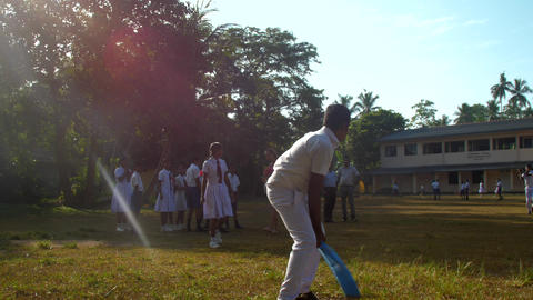 Sinhalese boy in school uniform misses cricket ball Archivo