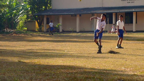concentrated Sinhalese schoolboy throws ball Archivo