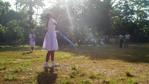 Sinhalese girl bats cricket ball and boys run Archivo
