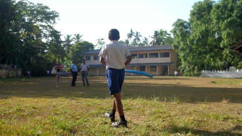 young Sinhalese pupil walks along green playground Archivo