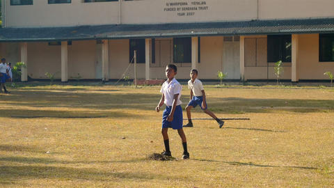 concentrated Sinhalese schoolboys play cricket Archivo