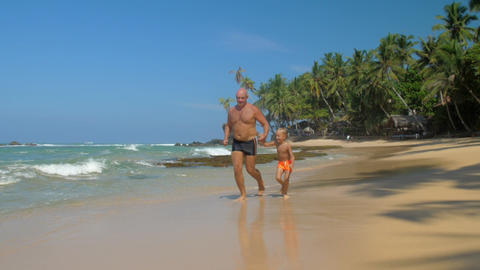 father and son run joining hands along beautiful sea beach Footage