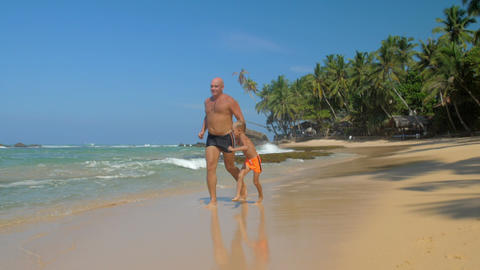 joyful boy and father spend time running along empty beach Footage