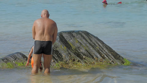 daddy helps son climb on wet rocks in clear ocean water Footage
