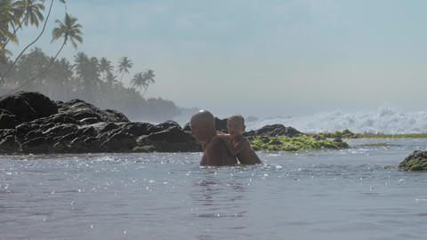 positive man with little son have fun in calm ocean water Footage