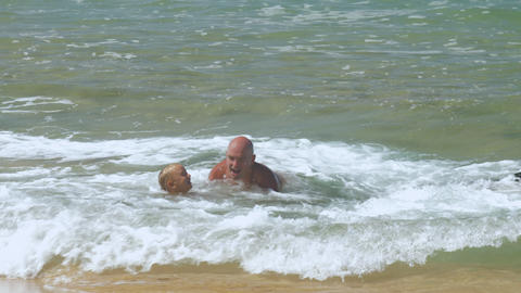 daddy plays with son in rolling sea waves at exotic resort Footage