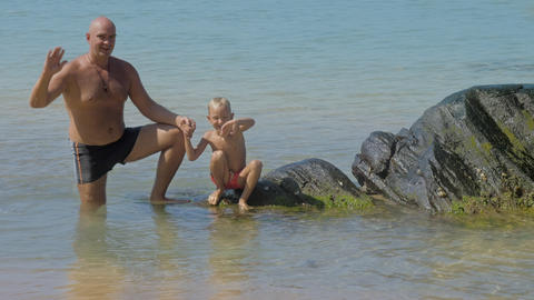 father and cute son wave hands at stones in shallow sea Footage