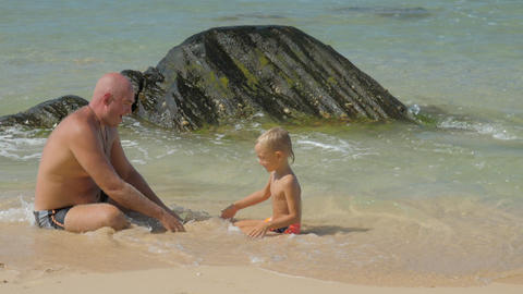family of father and son rests in clear sea water on beach Live Action
