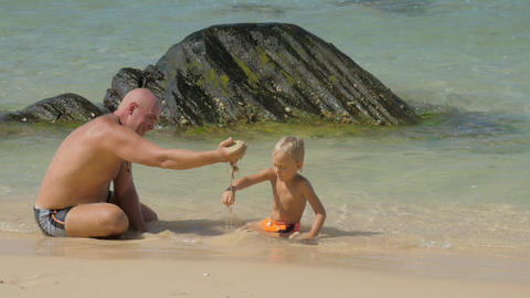 father shows wet sand to funny son resting in sea water Footage