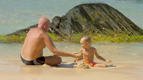 boy and father play with wet sand at ocean at exotic resort Footage