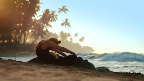 exciting lady does yoga near burning incense stick at ocean Footage