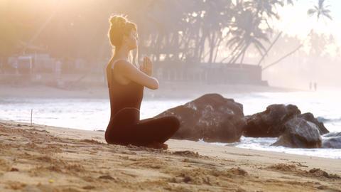 lady does yoga on sandy beach near burning incense stick Footage