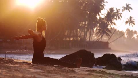 tremendous lady practices yoga on sandy beach near stones Footage