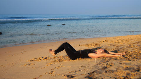beautiful lady in tracksuit practices yoga exercise on beach Footage