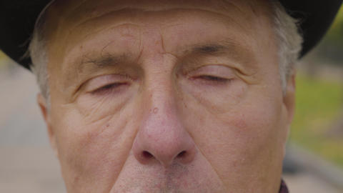 Extreme close-up of a Caucasian man with hazel eyes and grey hair looking at the Live Action